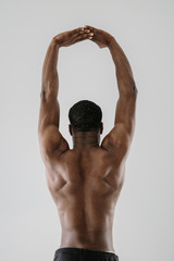 Rear view of topless sportsman with arms raised above head
