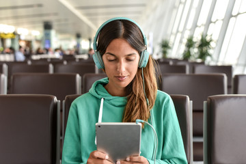 Young woman using tablet and listening to music at airport