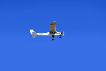 Samolot sterowany radiowo w powietrzu na błękitnym niebie.