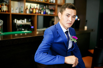 The groom in a blue suit is sitting in a bar with a buttonhole on his lapel, waiting for the bride, a portrait of a handsome man.