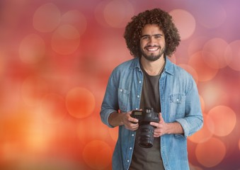 happy young photographer with camera on hands. Red bokeh