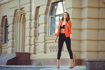 Fashion beautiful woman in red jacket and black bra and pants on city background