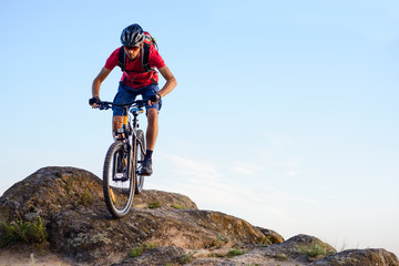 Cyclist in Red Riding the Bike Down the Rock on the Blue Sky Background. Extreme Sport and Enduro Biking Concept.
