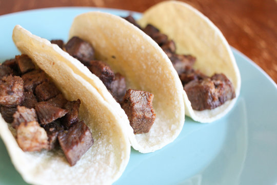 Tacos with steak on a blue plate on a wood background