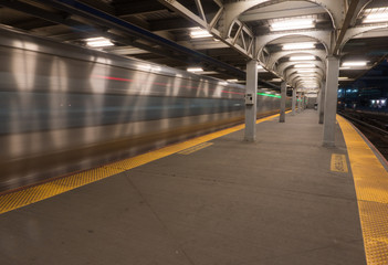 Long exposure motion blur of railroad train passing station platform at fast high speed