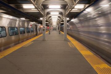 Long Exposure of high speed train passing station platform waiting departing train at railroad terminal hub