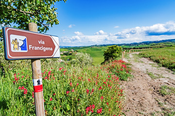 Via Francigena pilgrim path, Tuscany, Italy: road sign at beautiful Tuscany landscape background, spring scenery. Via Francigena is famous pilgrim path and popular travel hiking trail. Fototapete