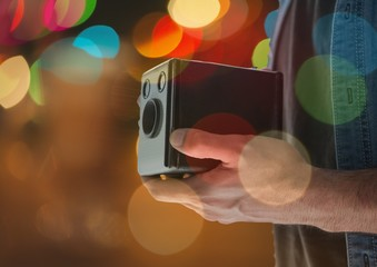 photographer hands with vintage camera at night. Color blurred