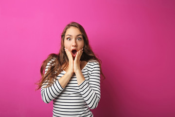 Portrait of young surprised woman on pink background
