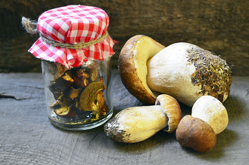 Dried mushrooms in a glass jar and fresh Boletus edulis mushrooms on old wooden table.Selective soft focus.