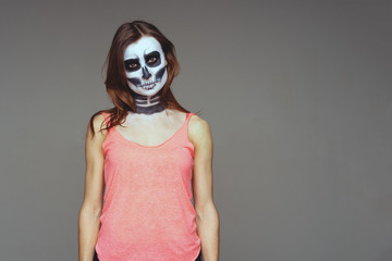 Portrait of brown-haired woman with terrifying halloween skeleton makeup in pink football and a tattoo on his arm over gray background looks at the camera