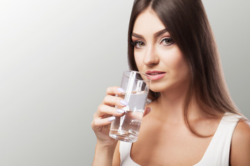 Drink water from the glass. Healthy Lifestyle. Portrait of a happy young woman with a glass of fresh water. Health. Drinks Beauty. The concept of diet. Healthy Eating.