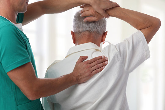 Senior man having chiropractic back adjustment. Osteopathy, Physiotherapy, pain relief concept