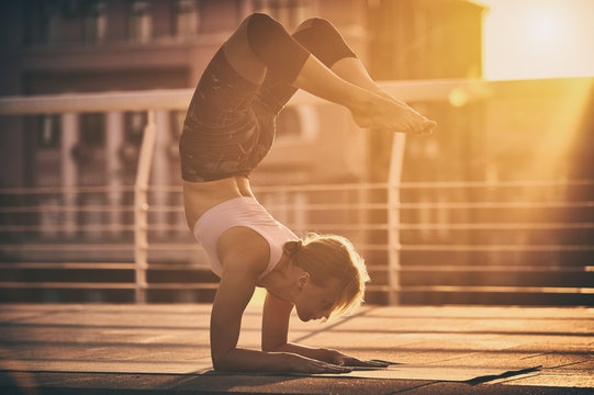 Young woman practicing yoga, standing in Vrischikasana Scorpion pose in the terrace at sunset