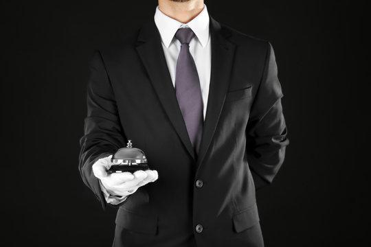 Man holding bell on black background