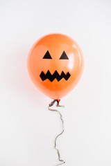 Halloween minimal concept. One orange balloon with scary face on white background. Flat lay, top view.