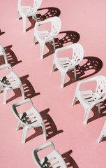 White chairs arranged opposite each other on pink background .