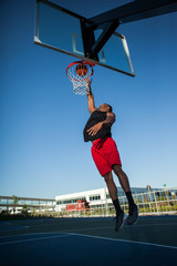 African American man dunking a basketball on an outdoor court