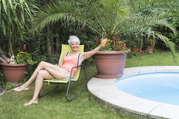 Cool happy senior woman holding a drink in the garden