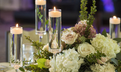 candles floating in stemware and roses for wedding reception