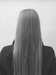 Teenage girl with long, straight hair, facing away