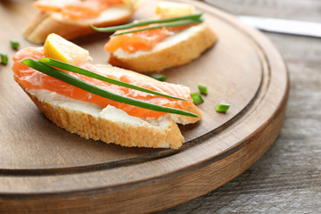 Delicious salmon bruschettas on wooden board, closeup