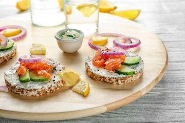 Tasty crispbreads with salmon on wooden board