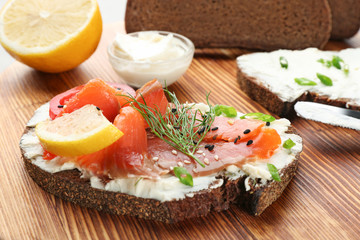 Tasty sandwich with salmon and creamy cheese on wooden background