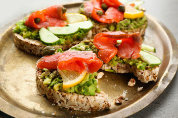 Tasty crispbread sandwiches with salmon and avocado on metal dish