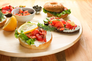 Tasty sandwiches with salmon on wooden board