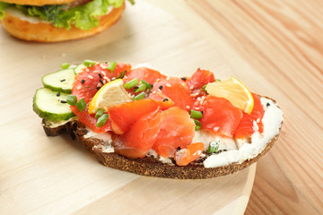 Tasty sandwich with salmon and creamy cheese on wooden board