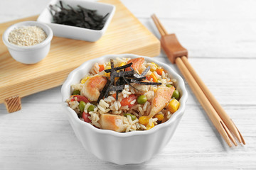Bowl with brown rice and vegetables on wooden table