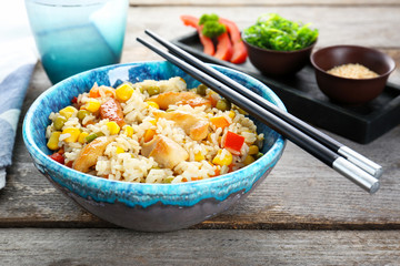 Bowl with brown rice, vegetables and chopsticks on table