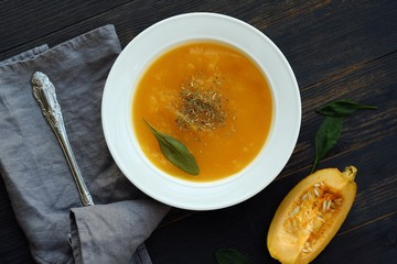 Delicious pumpkin soup with autumn herbs on the table