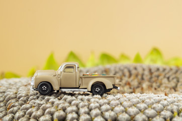 A little toy farm pickup truck on sunflower seeds.