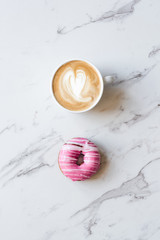 iced donut with striped pattern on a marble background