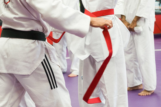 Martial Arts Teach putting on Student's Red Belt