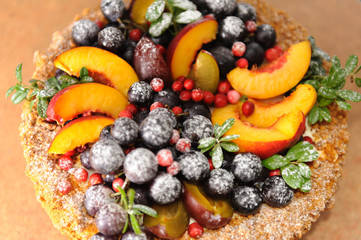 Birthday cake with fruits and berries in a powdered sugar stands on the table. View from above. Idea for the catalog. Idea for the menu