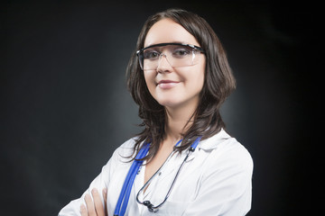 Caucasian Female Practiotioner Posing in Protective Glasses and Professional Endoscope Against Black Background.