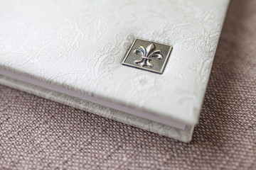 Photo book with a cover of genuine leather. White color with decorative stamping . Soft focus.