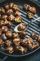 Close-up of roasted chestnuts in cast iron grilling pan over dark blue shabby plywood background, top view, selective focus, vertical composition