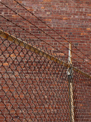 Chain link fence with barbed wire in front of a brick wall
