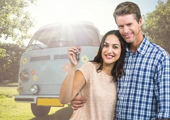 Couple holding keys in front of Camper van