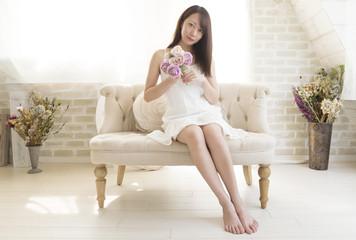 ソファーに素足で座る女性 夏服