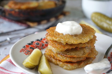 Fried potato fritters with sour cream