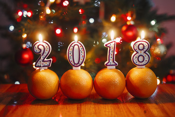 Oranges and lighted number candles on a table in the background of lights. the concept of Happy New Year 2018