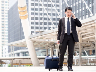 Portrait middle aged asian businessman 40s in the city, businessman, manager, boss handsome looking talking on the phone and holding bag in the city concept.