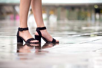 Close up woman legs with high heels on wet floor, rainy season
