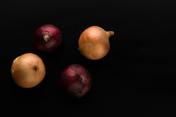 raw and unpeeled onion in red and golden colors on black background top view