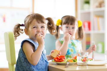 Cute little children eating food at daycare